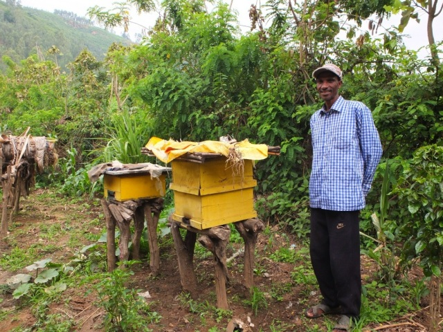 Marcos standing proudly next to his Modern beehives